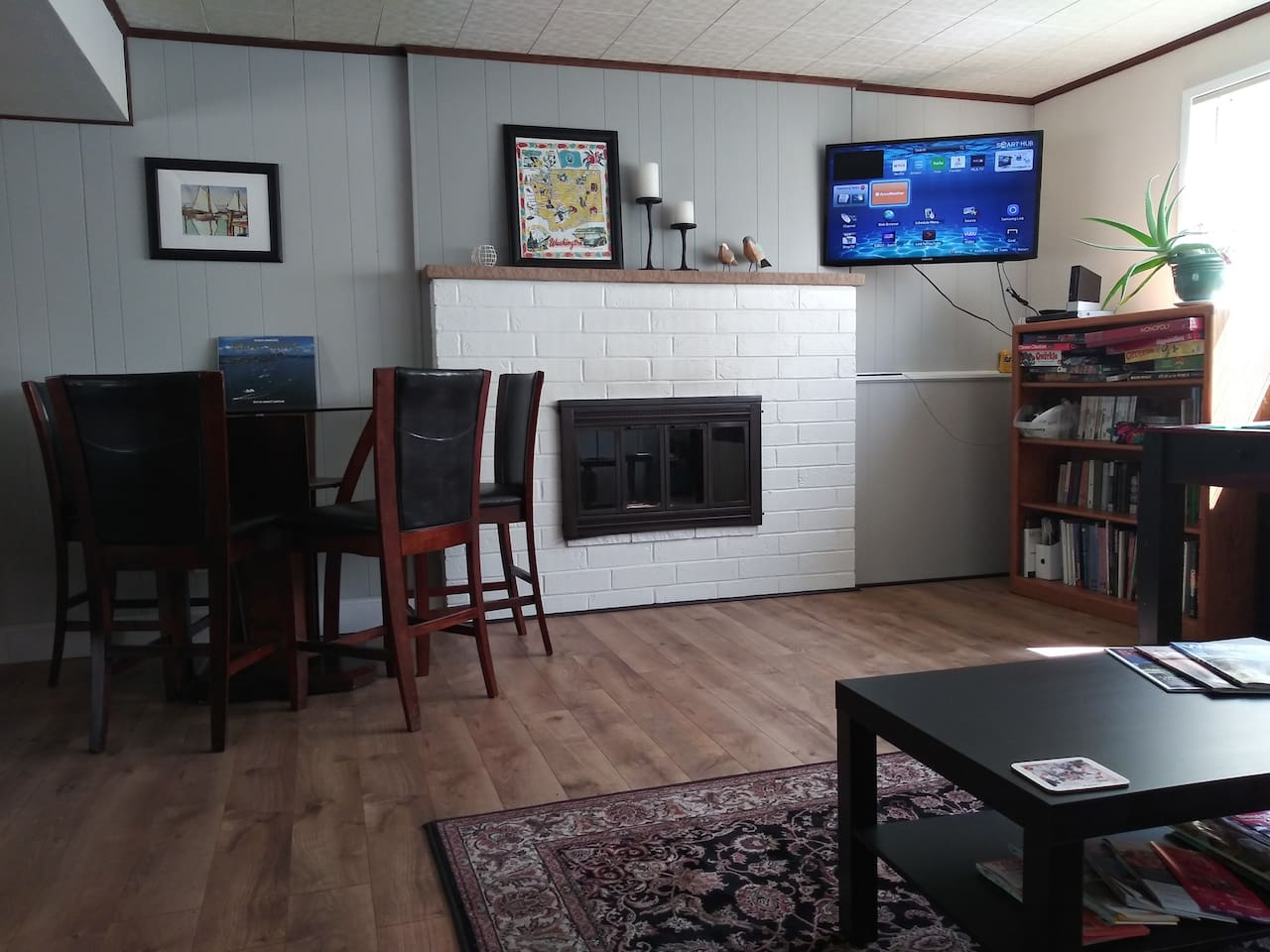 "Relax with this view from futon couch.  42"" Smart TV with Amazon Prime Video Complementary!  Wii Game console/books and games.  Two large windows for lots of natural light!  Fireplace with Mantle!"