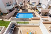View from roof terrace onto main balcony first floor with BBQ and seating area overlooking the pool.