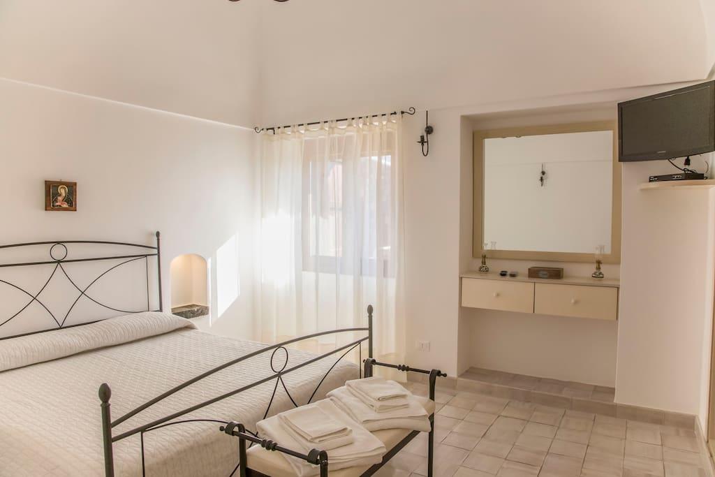 Prima camera da letto con specchiera e TV