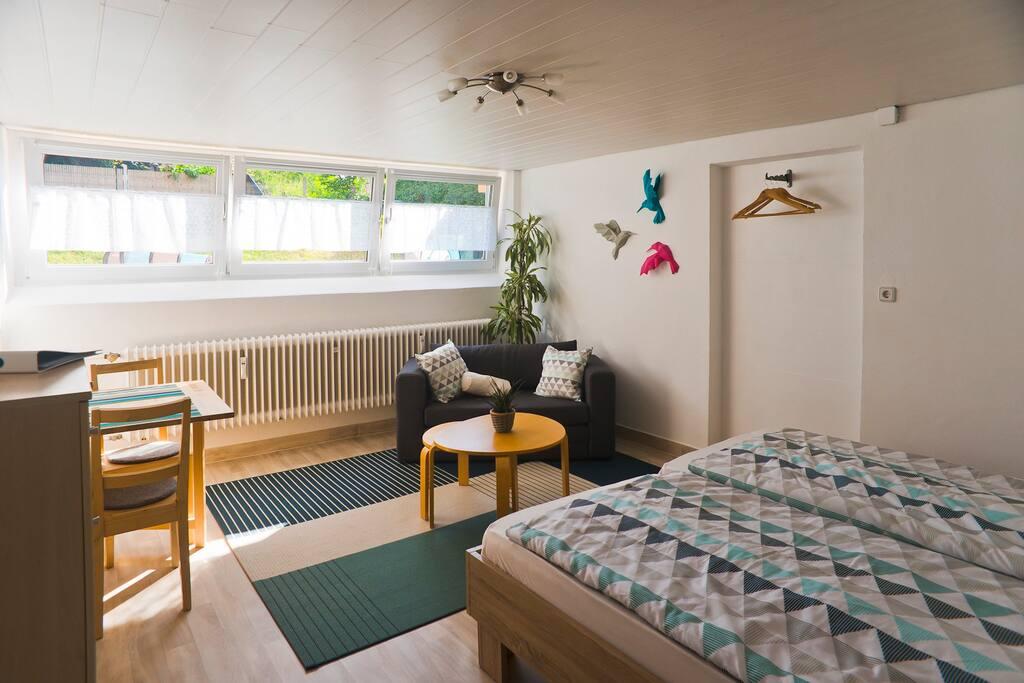 Der 20 qm große Wohn- und Schlafbereich bietet dank Fensterfront zum Garten eine helle, wohnliche Atmosphäre