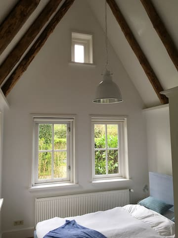 The bedroom has a high ceiling with beams