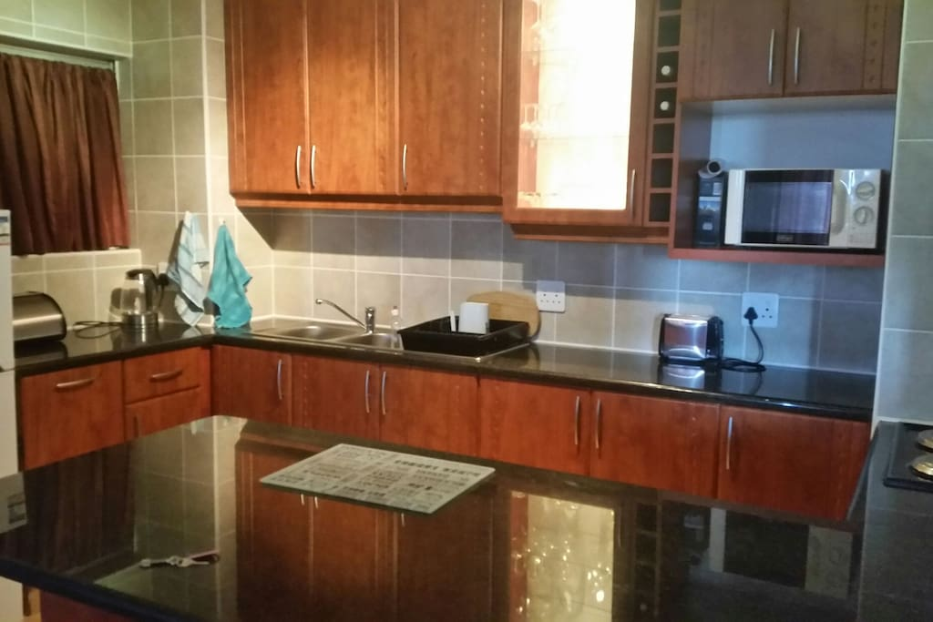 The stunning cherry kitchen featuring granite tops,  two fridges,  a microwave, oven and stove as well as all the other amenities.