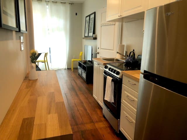 kitchen with electric stove and range, sink, fridge and freezer, kitchen tools.
