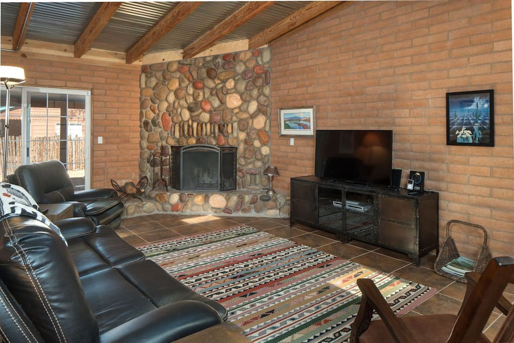 living room showing stone fireplace and flat screen TV