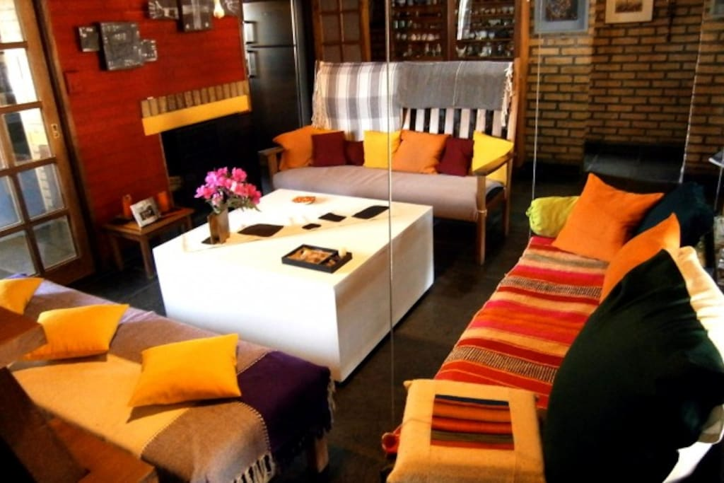 living, hogar a leña, mesa y sillones.