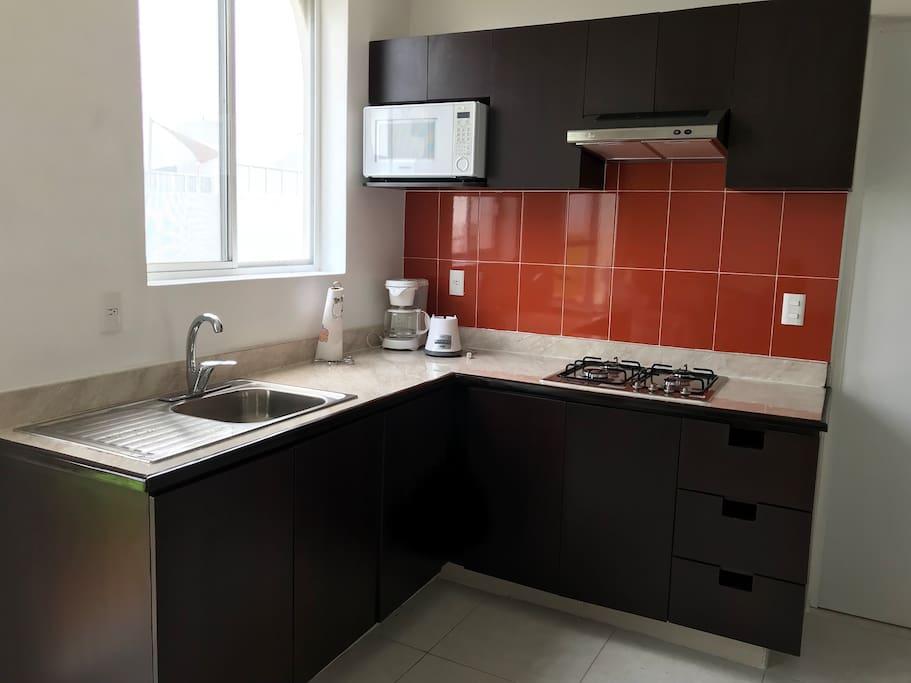 Cocina integral equipada con trastes, licuadora, vasos, platos, cubiertos, etc.