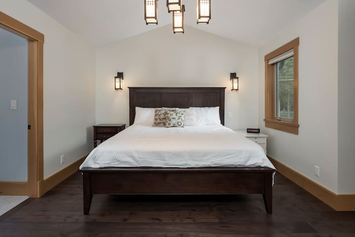 Master bedroom with a luxurious King sized bed, walk-in closet, and private ensuite