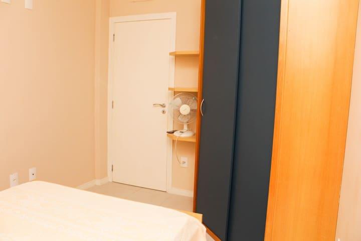 Ventilador e armário com cabides no quarto de casal