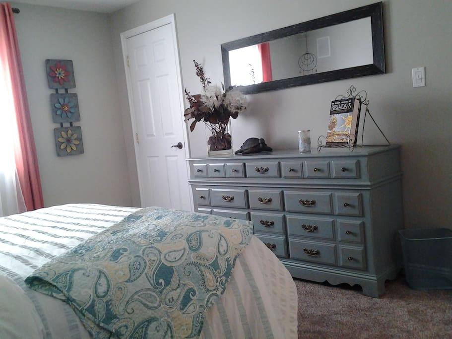 Bedroom w/queen size bed and dresser with walk in closet.