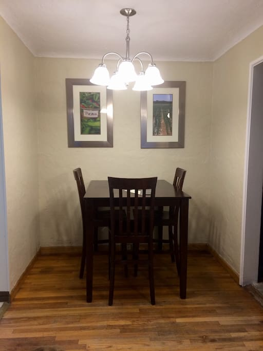 A tall but small dining table is towards the back of living room and just off the kitchen. We got quite a deal on the table and chairs because they're pretty scratched up, but will be beautiful some day. We only have three chairs for the table and they too need to be refinished too.
