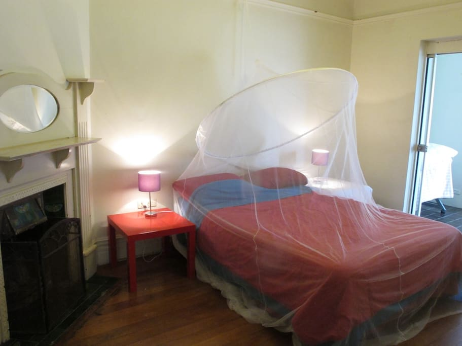 Double bed with mosquito net for summer - leads to sunroom with park and city views