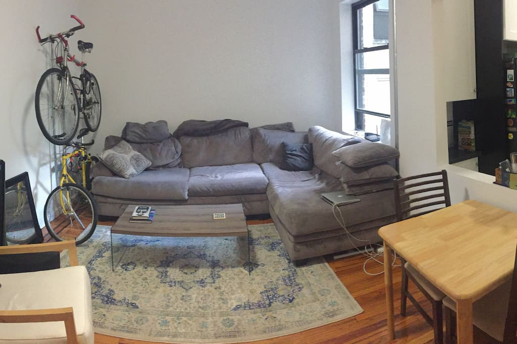 Large, relaxed living room with very comfy couch, dining area, video and music streaming