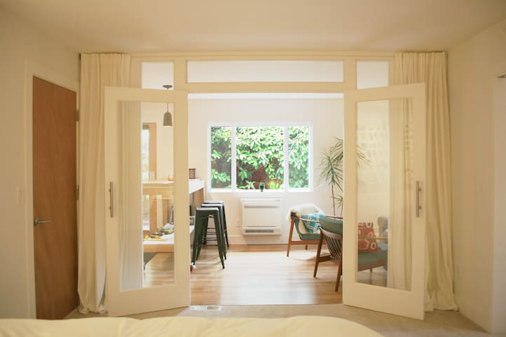 Master suite with French doors open to morning sun and private patio.
