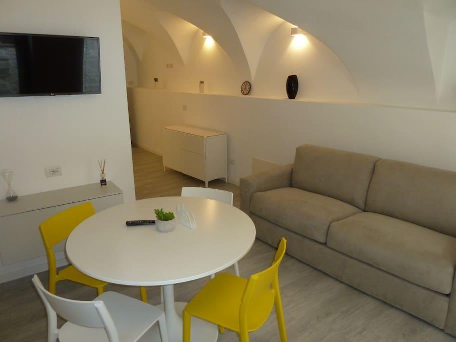 Wohnbereich mit Esstisch, Couch und SAT LCD