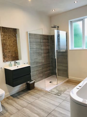 Spacious shared bathroom with walk in shower and jacuzzi bath