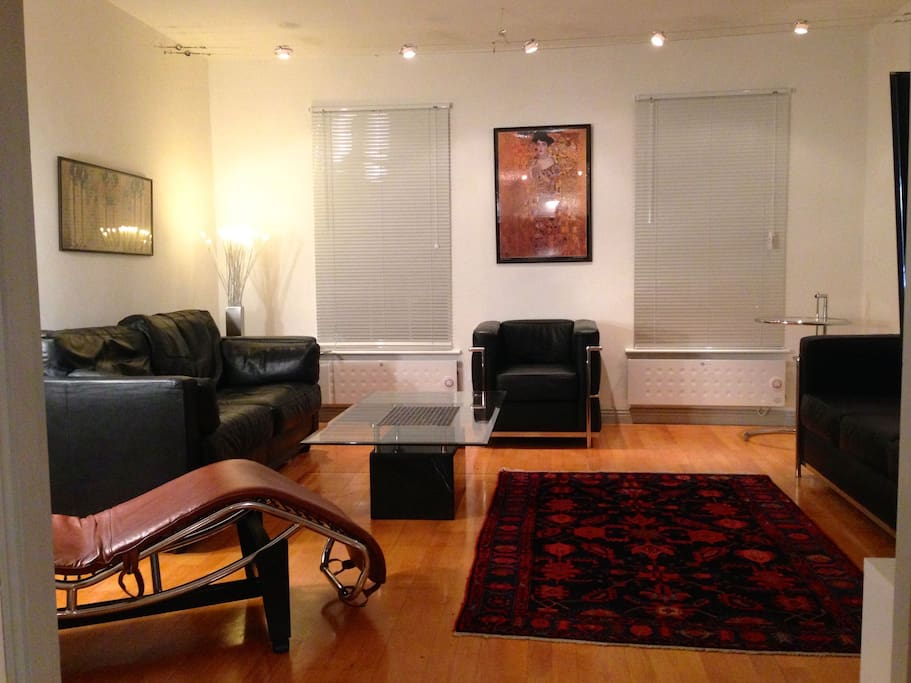 Living room with leather settees and marble/glass tables. Persian rug