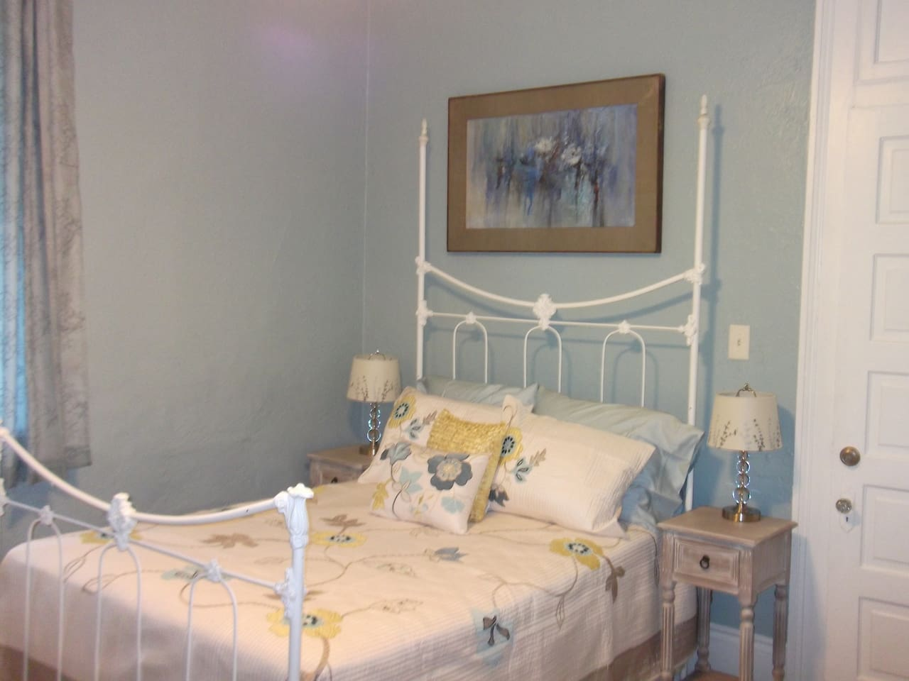 Bedroom #1 furnished classically with local New Orleans art
