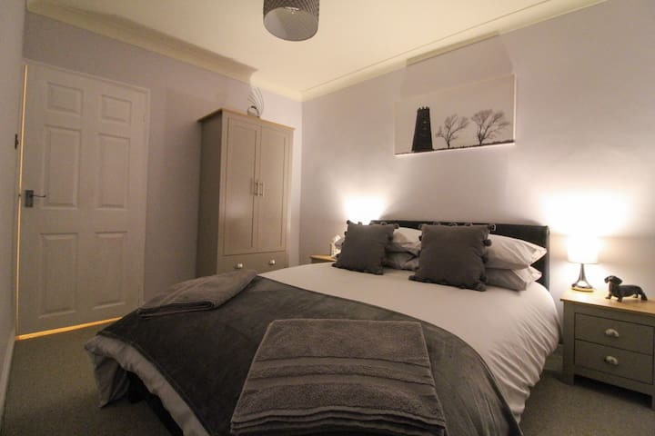 The smaller double bedroom has a double bed and a double wardrobe with drawers beneath.