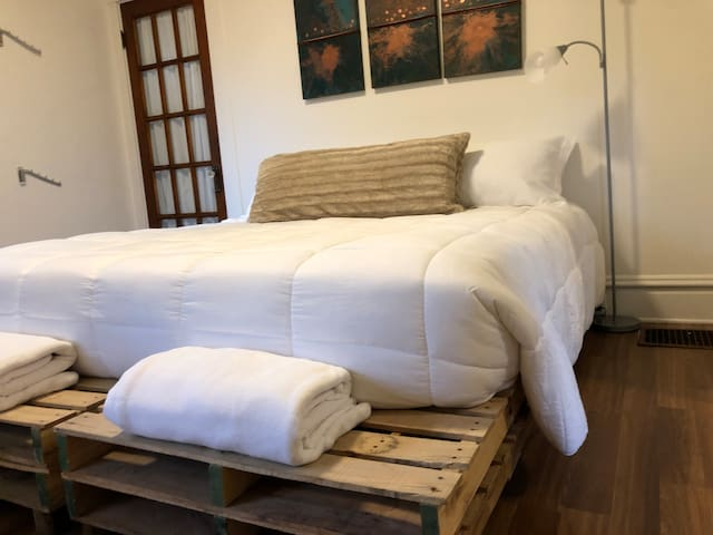 The bedroom area features a king-size bed with white linens, all of which rests on top of a modern pallet bed frame with custom glass end tables. The bedroom also has a place to hang clothes, an iron and ironing board, a mirror, and extra blankets