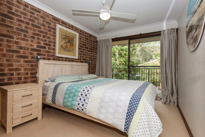 Main bedroom with queen bed and balcony.