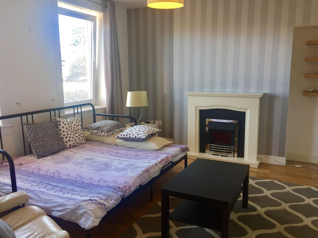 Large bedroom with king size sofa bed, double glass with shades, comfy armchair, tables, full size mirror and central heating.