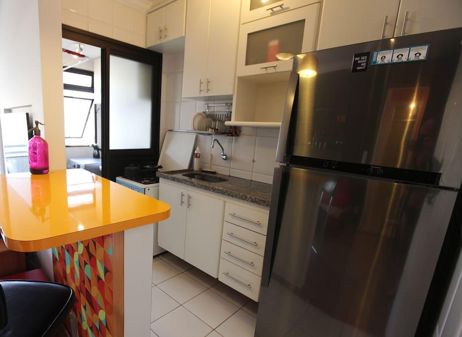 Cozinha americana com estrutura para o hospede cozinhar e lavanderia ao fundo.