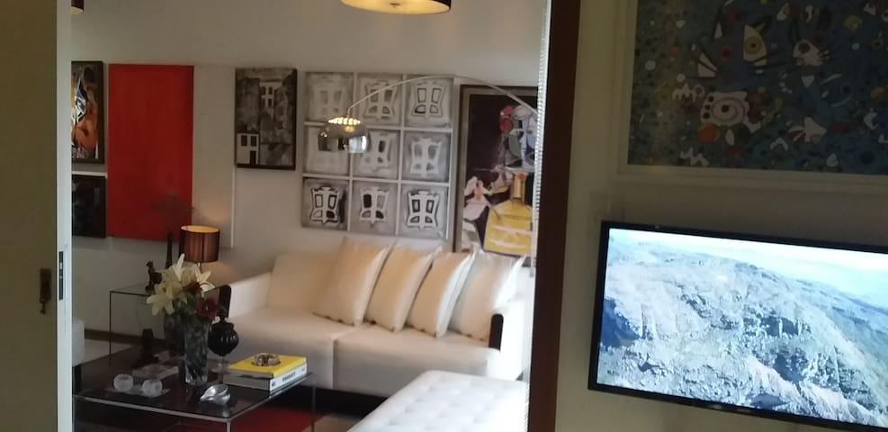visão da cama para a sala, detalhe: Smart Tv ao lado direito