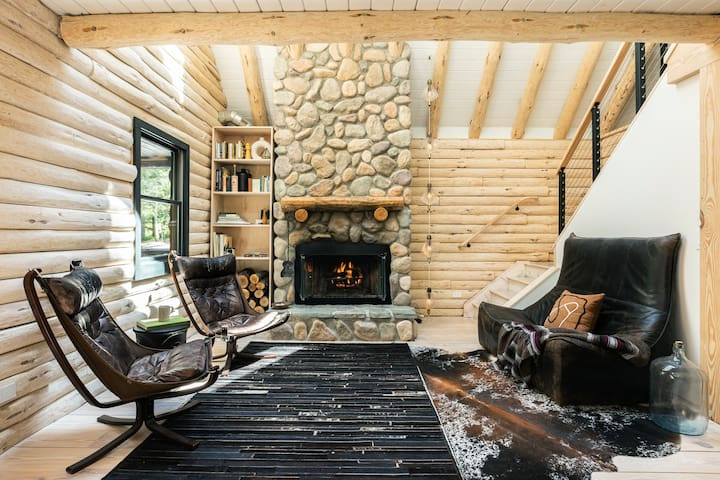 The cabin has a wood-burning fireplace accompanied by Sigurd Ressel sling chairs, a Gerard Van Den Berg sofa, and a vintage hanging string light.