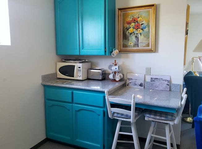 In addition to the dining area table with seating for 4, the cheery kitchen area has a roll-in mini breakfast bar, 2-burner electric hotplate, microwave, toaster, refrigerator, complimentary hot drinks and a roll-in sink for wheelchair accessibility.