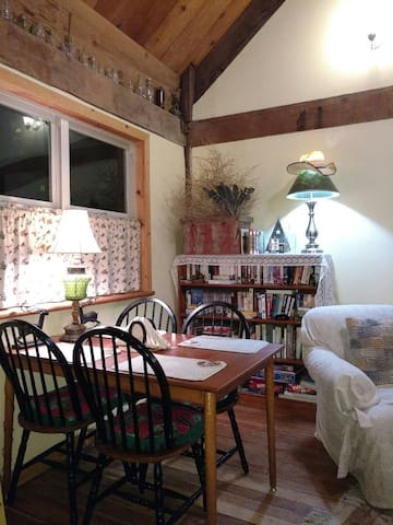 Dining area with easterly view of upper meadow features glass apothecary collection, library of games, videos and books.