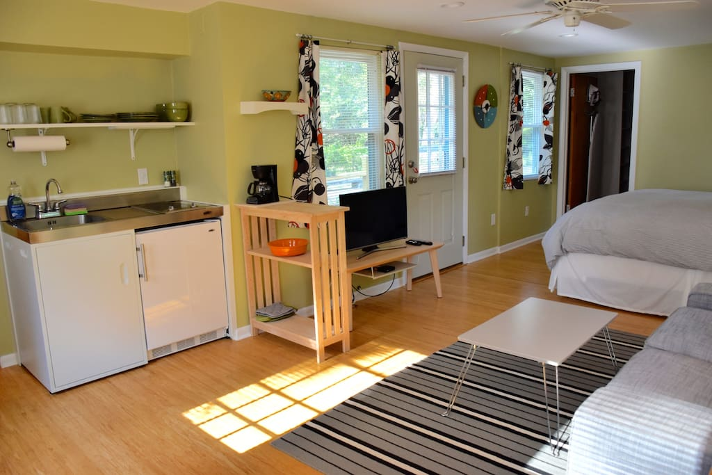 Kitchenette to left, flat screen smart tv, exit to private deck.