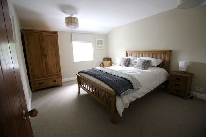King sized bed with top quality sprung mattress and additional mattress topper in a calm and tranquil bedroom