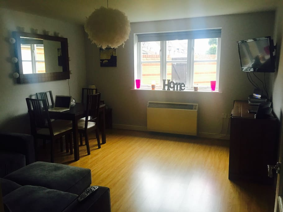 """Really bright living room with gorgeous comfy sofa. There is a bit of grass with a wall outside which is great as it gives you privacy (no one can access the grassed area). There is also a 32"""" TV and Sky, and a dining table to eat from / work off"""