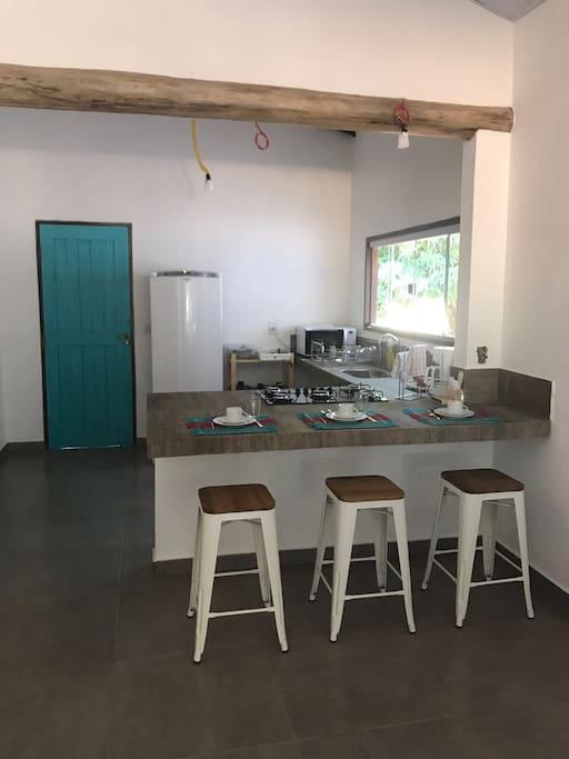 Cozinha equipada com fogão, geladeira, microondas, panelas e utensílios