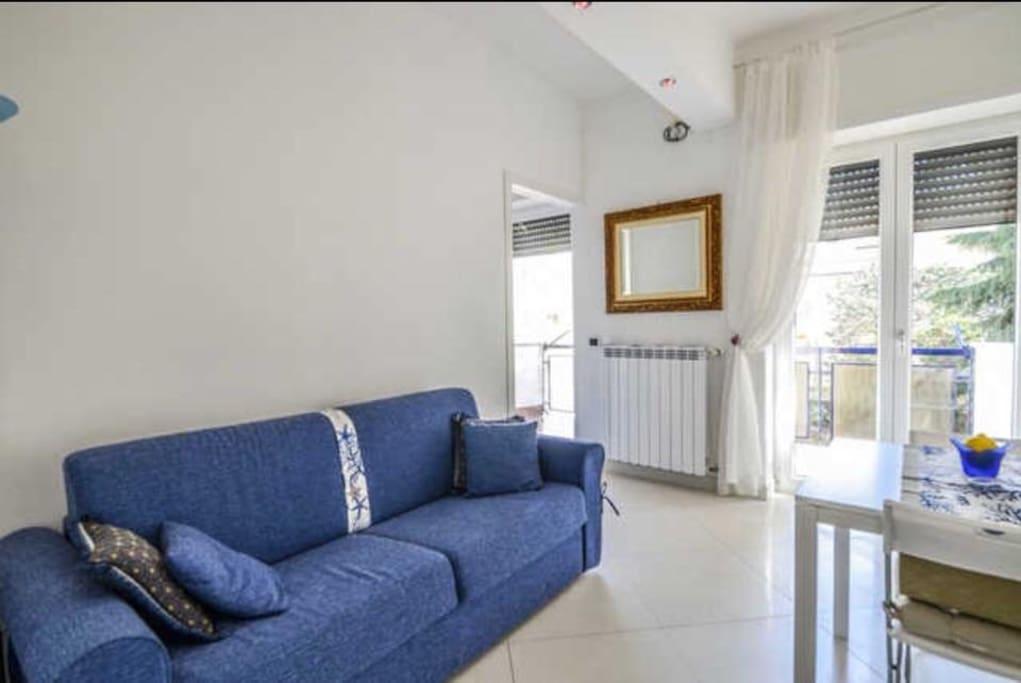 Ingresso in soggiorno con angolo cottura tavolo con sedie e divano letto.