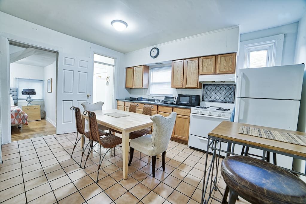 Kitchen with cookware, dishes, utensils, microwave, toaster oven, coffee maker, stove, fridge.