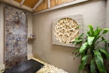 The shower are with bali style stone carving and pebbles