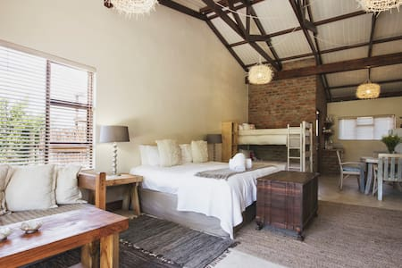 Open plan family suite with king bed & 2 bunk beds. Kitchen. Built in fireplace. Free wi-fi. DSTV and dvd player.