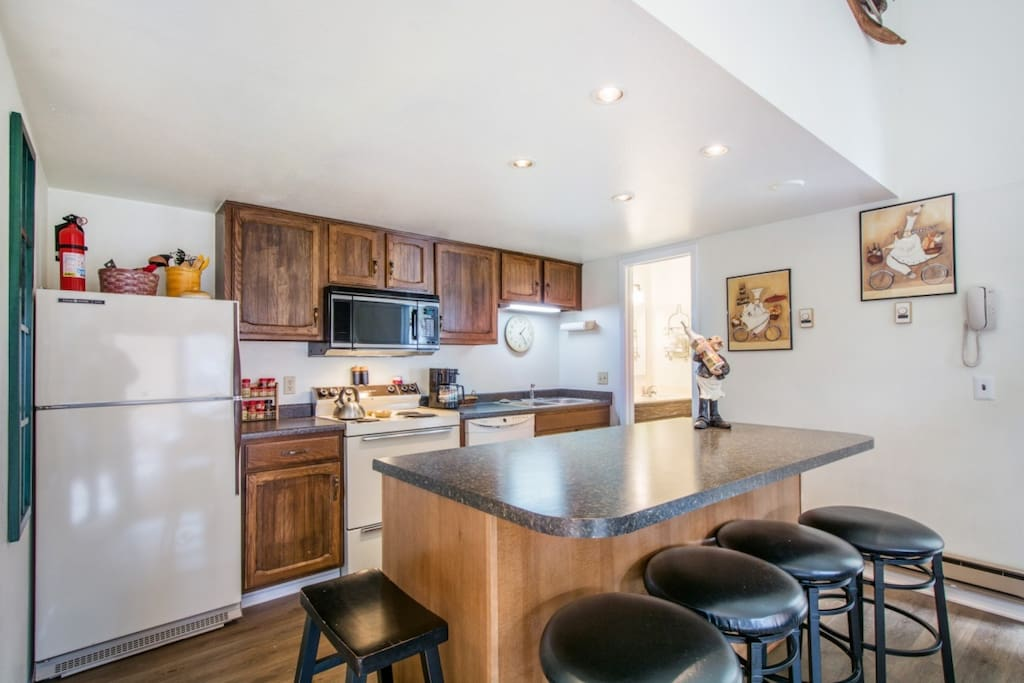 The renovated kitchen has an open layout and features a brand new kitchen island with breakfast bar, new cabinets, counters & recessed lighting.