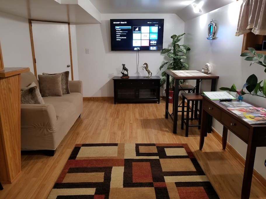 """2 of 2 Views of Living Room Space. Featuring a 55"""" 4K Smart TV, Dining Table & Magazines"""