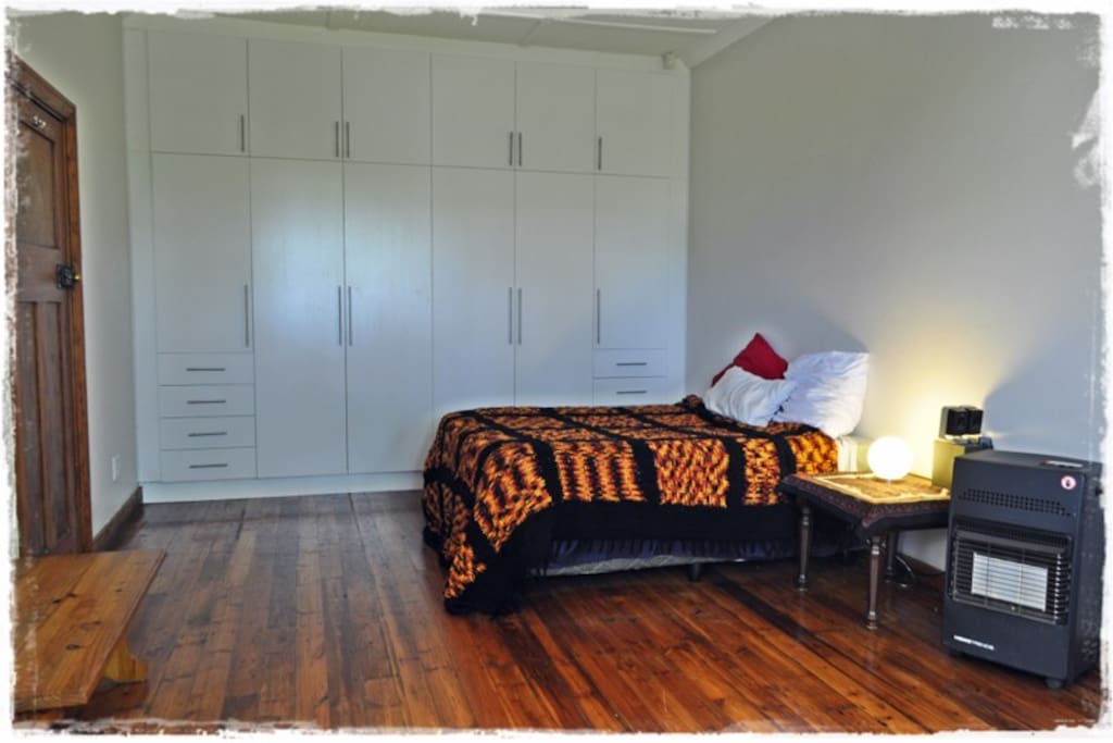 This photo shows the first half of the bedroom where you will have a double bed with homely clean linen and large amounts of cupboard space. There is a gas heater with gas filled for your convenience should you get cold in the winter
