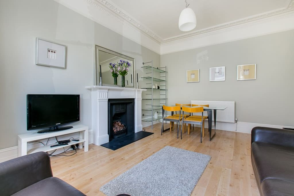 large sitting room with double sofa bed, dining table for 4 and TV