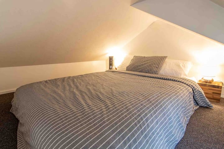 Loft bed space. Access via secured ladder. Queen bed with small fan and touch lamps help to make for a cozy resting/sleeping area.
