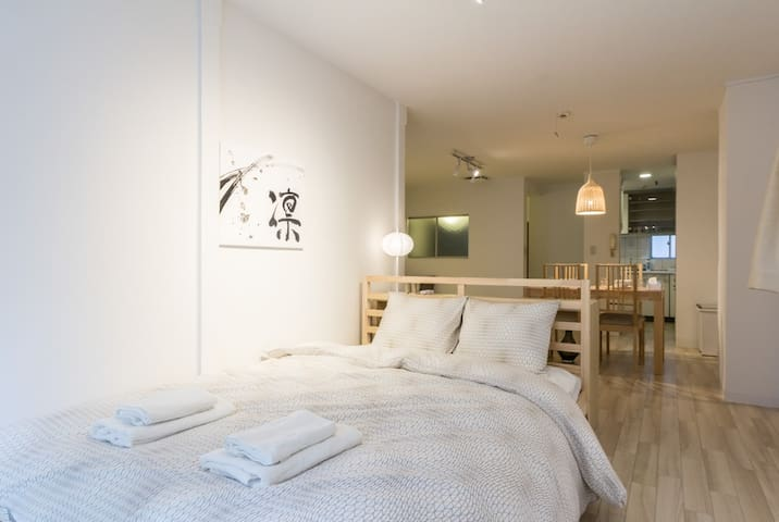The double bed in the living space, facing back into the apartment