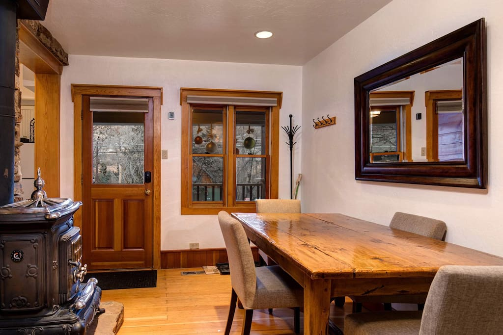 The natural-finish wood dining table has seating for four in the dining area.
