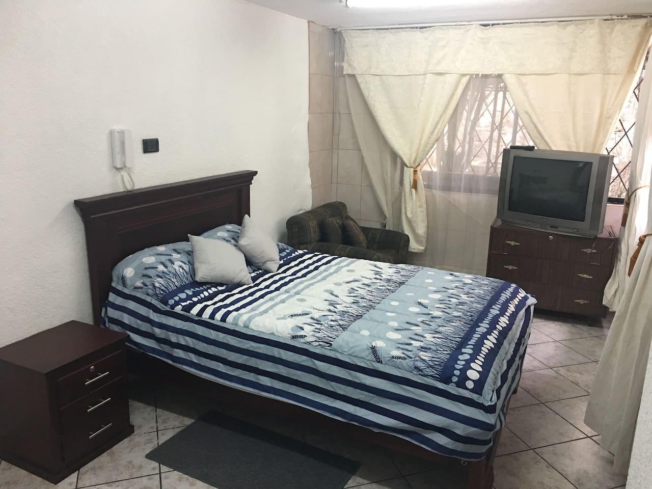 cama con velador, cajonera y televisión