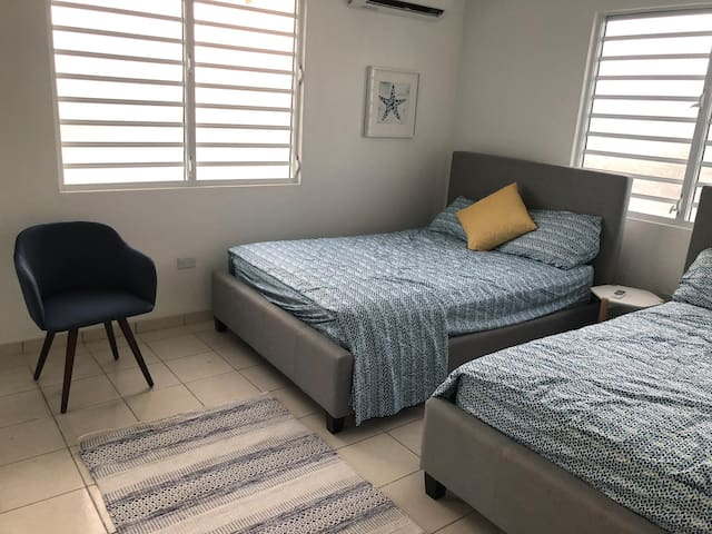 Room with 2 full beds with air conditioner.