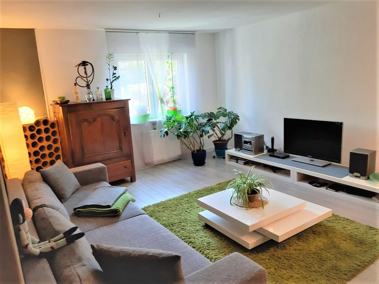 spacious living room with a sleeping sofa and a TV