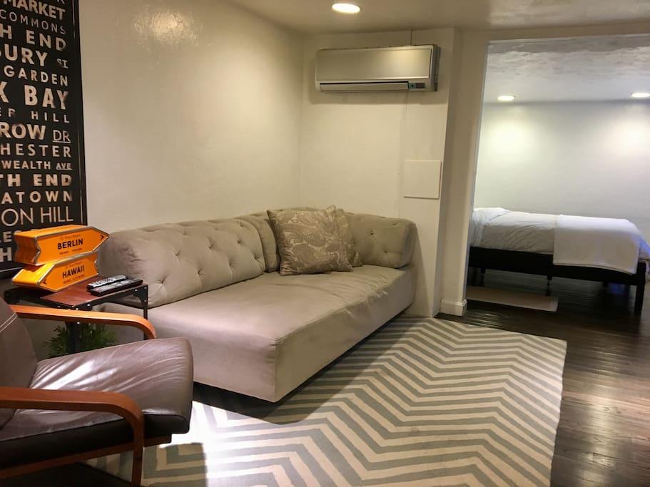 Big couch in living room, open to bedroom.
