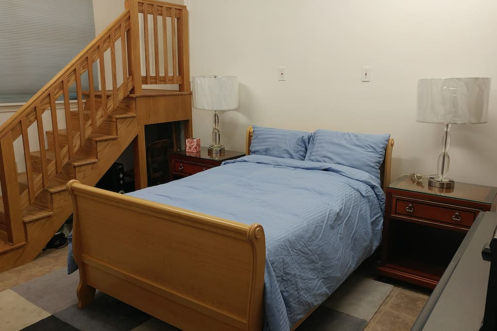 Full size bed with left and right nightstands; stairs to inaccessible storage area